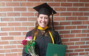 Laura Kuglitsch smiling in her cap and gown at her master's graduation in 2018.