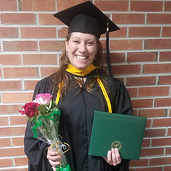 Headshot of Laura Kuglitsch in her cap and gown, holding her diploma at graduation.